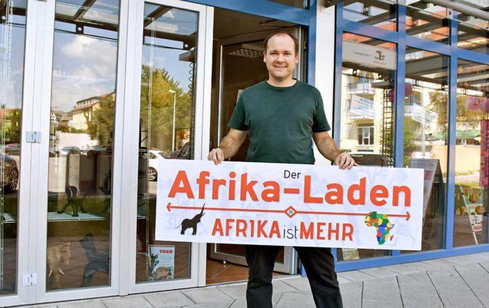 Andy Kopp hält das Schild des Afrika-Ladens in Fürstenfeldbruck