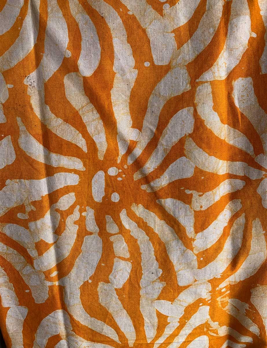 Gebatikter afrikanischer Stoff in Orange und Weiß und rundem Wellen-Muster